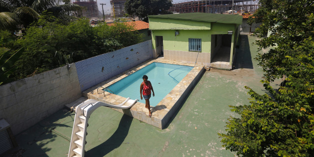Marcias Lemos, 57, walks by a pool in her house, with cranes and construction work for the Rio 2016 Olympic Park seen in the background, at the Vila Autodromo favela in Rio de Janeiro January 28, 2015. Street addresses jump in the Vila Autodromo favela: 39, 42, 48, 51. The missing numbers belonged to homes now reduced to rubble to make way for the Olympic Park in Rio de Janeiro. But 18 months before the Olympic Games begin, about 50 families still refuse to leave, clinging on despite increasing