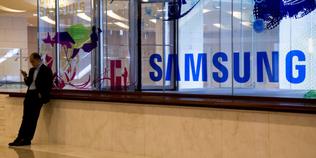 A man uses a mobile device in front of Samsung Electronics Co. signage at the company's D'light flagship store in Seoul, South Korea, on Wednesday, Oct. 12, 2016. Samsung halted sales of its Galaxy Note 7 smartphones and asked consumers to stop using the ones they've already purchased, another blow to South Korea's largest company as it struggles with a crisis over exploding batteries. Photographer: SeongJoon Cho/Bloomberg via Getty Images