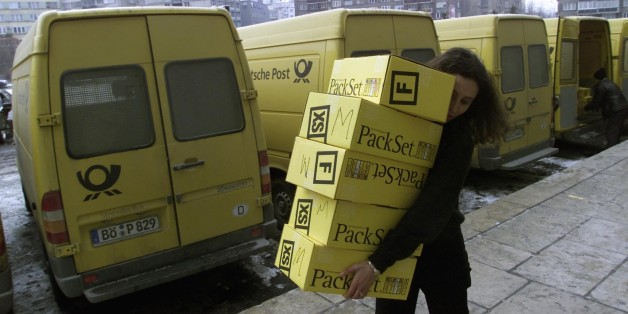 A Romanian woman carries boxes with childrens' toys December 18, 2001