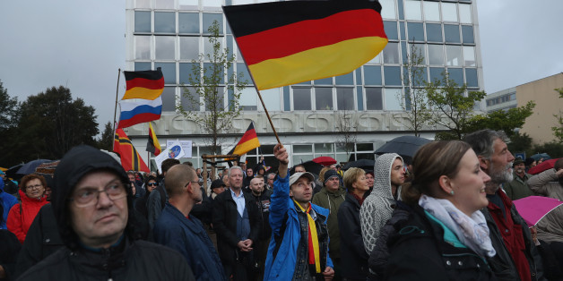 DRESDEN, GERMANY - OCTOBER 03:  Supporters of the Pegida movement, including some waving German flags, listen to speeches after marching on German Unity Day on October 3, 2016 in Dresden, Germany. Unity Day, called Tag der Deutschen Einheit, commemorates German reunification of East and West Germany following the end of the Cold War. This year's main celebrations are taking place in Dresden and are being accompanied by protests from both left and right-wing groups, notably the anti-Muslim and an