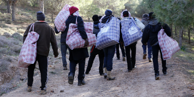 In this photo dated Saturday, Feb. 14, 2015, migrants head back to their mountain camp near the coast city of Nador, northern Morocco, carrying bags of food and clothing provided by Asticude, a Moroccan organization involved with immigration issues. Moroccan security forces raided a makeshift mountain camp and arrested hundreds of illegal migrants in a crackdown aimed at halting the constant attempts to storm Spain's North African enclave of Melilla. (AP Photo/Abdeljalil Bounhar)