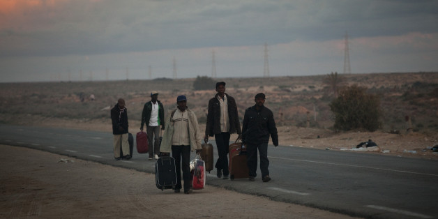 Men from Ghana, who used to work in Libya and fled the unrest in the country, carry their belongings as they arrive in a refugee camp after crossing from Libya at the Tunisia-Libyan border, in Ras Ajdir, Tunisia, Tuesday, March 22, 2011.  (AP Photo/Emilio Morenatti)