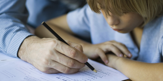 Male junior high student watches as teacher corrects assignment, close-up