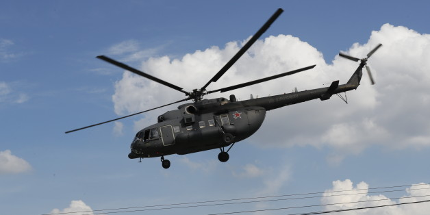 A Russian military Mi-8 helicopter flies away from the Defense Ministry headquarters in downtown Moscow, Russia on Monday, Aug. 1, 2016. (AP Photo/Alexander Zemlianichenko)