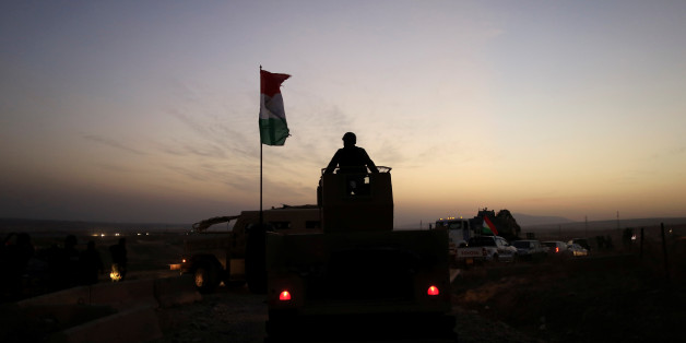 A Kurdish Peshmerga fighter looks over as he stands on the top of a humvee in front of an Islamic State militants' position outside the town of Naweran near Mosul, Iraq October 20, 2016. REUTERS/Zohra Bensemra     TPX IMAGES OF THE DAY