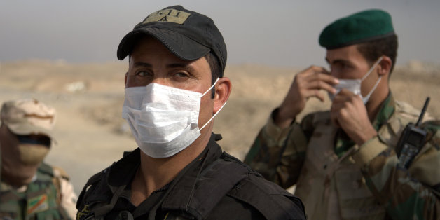Iraqi troops wear masks as they guard a checkpoint near the village of Awsaja, Iraq, as smoke from fires lit by Islamic State militants at oil wells and a sulfur plant fills the air. U.S. military officials say that a fire at a sulfur plant in northern Iraq set by Islamic State militants on Thursday is creating a potential breathing hazard for American forces and other troops at a logistical base south of Mosul. (AP Photo/Adam Schreck)