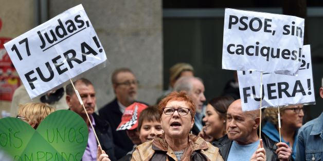 A PSOE supporter holds placards reading '17 Judas out' 'PSOE without chiefs' outside the Spanish Socialist Party (PSOE) headquarters in Madrid during an extraordinary meeting of the PSOE Federal Committee, on October 23, 2016.Spain's embattled Socialists gather today for a crunch strategy meeting expected to see the party lift its veto on a minority conservative government and finally unblock the country's ten-month political deadlock. / AFP / GERARD JULIEN        (Photo credit should read GERAR
