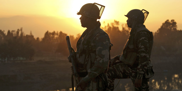 Indian soldiers stand guard near a building where suspected militants have taken refuge during a gun battle in Pampore, on the outskirts of Srinagar, Indian controlled Kashmir, Tuesday, Oct. 11, 2016. A handful of rebels holed up in a building in the Indian portion of Kashmir exchanged fire with government forces for the second straight day on Tuesday. (AP Photo/Mukhtar Khan)