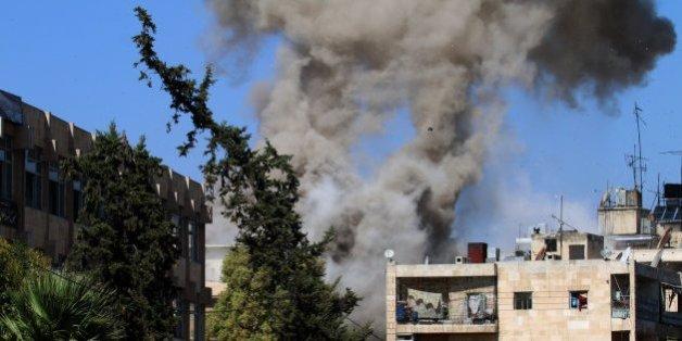 De la fumée s'échappe d'un immeuble dans un quartier tenu par le gouvernement à Alep, le 20 octobre 2016.