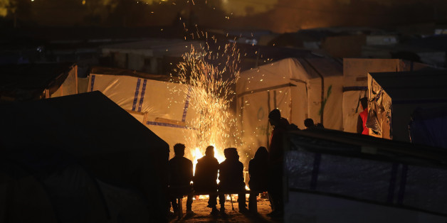 CALAIS, FRANCE - OCTOBER 24:  Migrants sit by a fire inside the Jungle camp on October 24, 2016 in Calais, France. Many migrants have left by coach to be reloctated at centres across France as Police and officials in France begin to clear the 'Jungle' migrant camp in Calais. Some 7,000 people are estimated to be living in the camp in squalid conditions.  (Photo by Christopher Furlong/Getty Images)