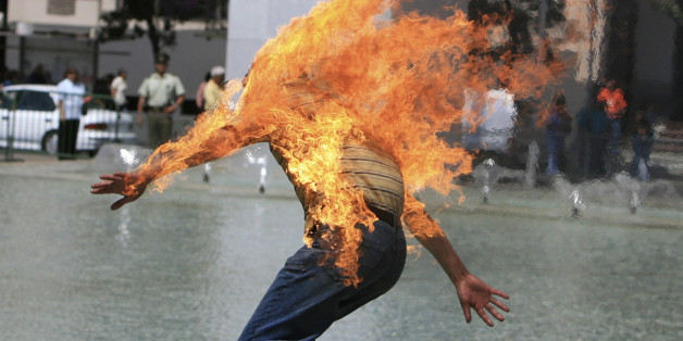 A housing debtor runs after setting himself on fire to protest against Chile's housing system in front of the government palace in Santiago January 4, 2007. The man extinguished the flames by jumping into a pool outside the government palace and was arrested by police.   CHILE OUT    REUTERS/Stringer (CHILE)