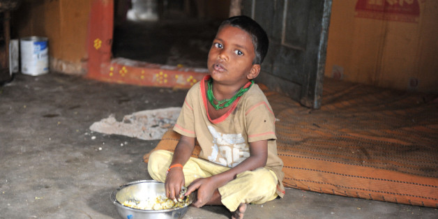 An Indian boy looks at the camera has he eats at his home in a slum in Hyderabad, on January 10, 2012. Levels of under-nutrition in the country were 'unacceptably high' despite impressive GDP growth, Prime Minister Manmohan Singh said Tuesday and added that the problem of malnutrition was a 'national shame'. AFP PHOTO / Noah SEELAM (Photo credit should read NOAH SEELAM/AFP/Getty Images)