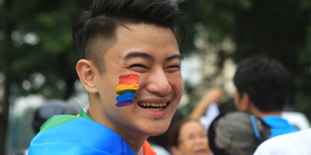 Nguyen Tran Dai Hai smiles during a gay pride parade in Hanoi, Vietnam, Sunday, Aug. 21, 2016. About one thousand people hit the streets of Hanoi to celebrate the annual gay pride parade and rally for human rights. (AP Photo/Hau Dinh)