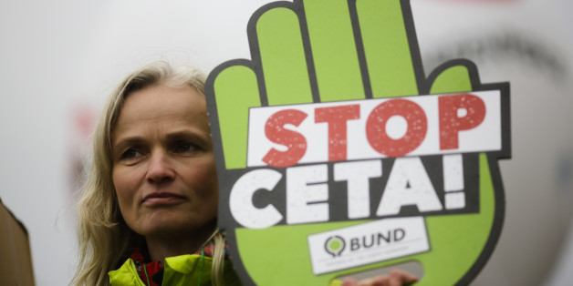 A demonstrator holds a poster against the Comprehensive Economic and Trade Agreement, CETA, during a protest in front of the chancellery in Berlin, Wednesday, Oct. 12, 2016.  The Federal Constitutional Court held a hearing Wednesday considering calls from opponents of a European Union-Canada trade deal for an injunction aimed at putting the signing of the accord on ice. (AP Photo/Markus Schreiber)