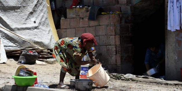 A Sub-Saharan woman does some washing-up at the bottom of a makeshift building where she lives with other fellow migrants in impoverished conditions, on May 29, 2016, in the capital Algiers.  In the past, Algeria was a land of emigration, millions of its citizens exiled to France, but in recent years it has become a destination country for many West Africans. Nigerians, Malians, Cameroonians, brave the horrors of the Sahara to find refuge in the largest country in Africa, as the crossing to Euro