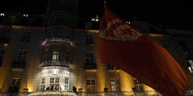 Well wishers hold a Tunisian flag as the Nobel Peace Prize 2015 winners, the members of the Tunisian National Dialogue Quartet appear on the balcony of the Grand Hotel in Oslo on December 10, 2015. The Nobel Peace Prize was awarded to four civil society groups, who led Tunisia's transition to democracy, though the country has now been plunged into a state of emergency as it battles the threat of jihadism. AFP PHOTO / ODD ANDERSEN / AFP / ODD ANDERSEN        (Photo credit should read ODD ANDERSEN/AFP/Getty Images)