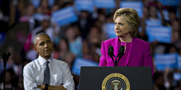 Hillary Clinton, presumptive 2016 Democratic presidential nominee, pauses while speaking as U.S. President Barack Obama, left, listens during a campaign rally at the Charlotte Convention Center in Charlotte, North Carolina, U.S., on Tuesday, July 5, 2016. Obama, making his debut campaign appearance on Clinton's behalf, flew with her on Air Force One as a show of unity and power hours after the FBI director called Clinton's handling of sensitive e-mails as Secretary of State extremely careless. P