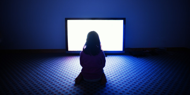 Girl sitting in front of flat screen television in dark room.