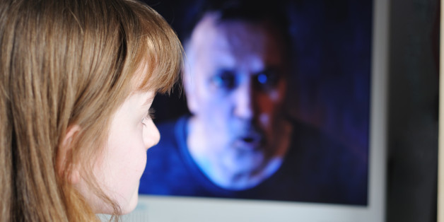 Child looking at horrible man on screen. Useful to show dangers of Internet or unsupervised viewing