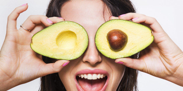 Beauty model holding avocado halves over her eyes