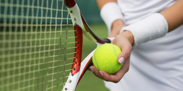 Close-up of tennis player holding racket and ball in hands
