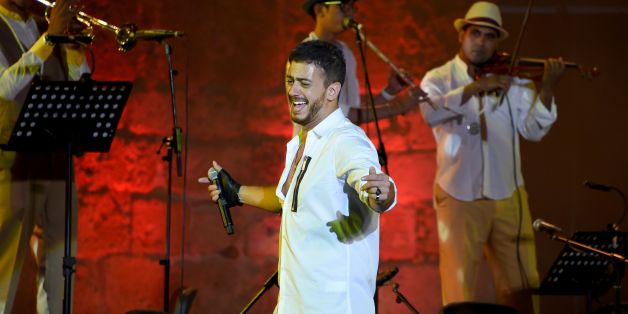 Morocco singer Saad Lamjarred performs with Ukrainian Orchestra Symphonic at the opening of the Carthage Festival on July 30, 2016 at the romain theatre of carthage near Tunis. / AFP / FETHI BELAID        (Photo credit should read FETHI BELAID/AFP/Getty Images)