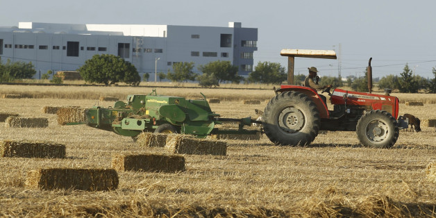 A tractor pulls a hay baler after reaping wheat at a field in Tunis June 18, 2014. REUTERS/Zoubeir Souissi (TUNISIA - Tags: AGRICULTURE SOCIETY)