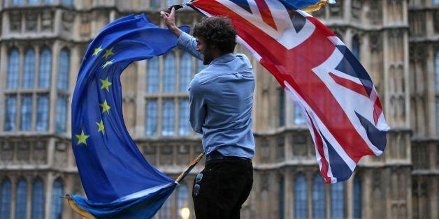 Ein Mann schwängt die Fahnen der EU und Großbritanniens vor dem britischen Parlament