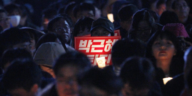 "A protester holds a placard and a candle during a rally, calling for South Korean President Park Geun-hye to step down in downtown Seoul, South Korea, Wednesday, Nov. 2, 2016. South Korean prosecutors requested an arrest warrant for a longtime friend of Park on Wednesday over allegations of influence-peddling and other activities that have triggered a huge political scandal that threatens Park's leadership. The placard reads: ""Park Geun-hye should step down."" (AP Photo/Ahn Young-joon)"