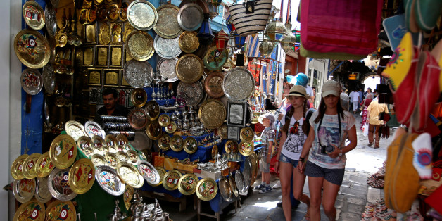 Tourists walk past traditional souvenirs displayed for sale in the old city of Tunis, Tunisia June 17, 2016. REUTERS/Zoubeir Souissi