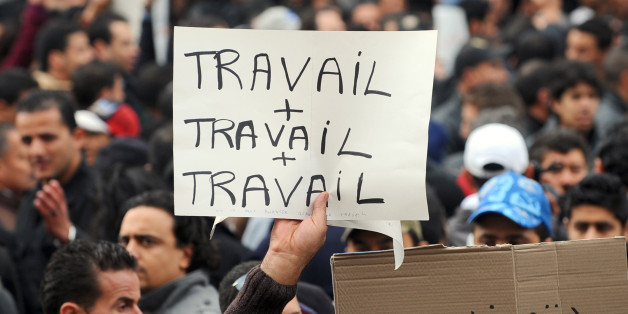 Tunisian pro-government demoNstrators hold placards reading at L (Work + work + work) and at R (Tunisia in arabic) during a protest on Habib Bourguiba avenue in Tunis on January 25, 2011. Hundreds of people taking part in the first rally backing Tunisia's new interim government were later chased away by protesters calling for the leadership to resign in chaotic scenes in Tunis. AFP PHOTO / FETHI BELAID (Photo credit should read FETHI BELAID/AFP/Getty Images)