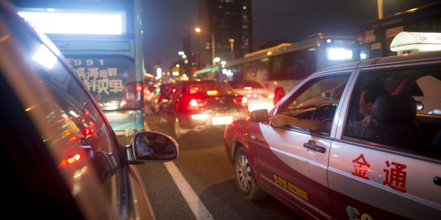 A taxi driver smokes a cigarette while waiting in traffic at night in the Luohu district of Shenzhen, China, on Monday, Aug. 4, 2014. China's consumer-price index (CPI) is scheduled to be released on Aug. 9. Photographer: Brent Lewin/Bloomberg via Getty Images