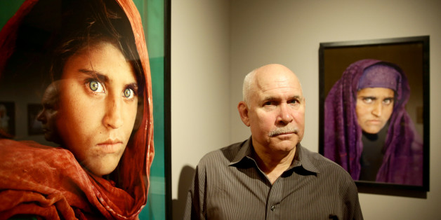 US photographer Steve McCurry poses next to his photos of the 'Afghan Girl' named Sharbat Gula at the opening of the 'Overwhelmed by Life' exhibition of his work at the Museum for Art and Trade in Hamburg, northern Germany on June 27, 2013. The exhibition comprises some 120 photographs taken between 1980 and 2012 in countries such as Afghanistan, the United States, Pakistan, India, Tibet, Kashmir, Cambodia, Indonesia, Burma and Kuwait. AFP PHOTO / DPA / ULRICH PERREY GERMANY OUT RESTRICTED TO ED