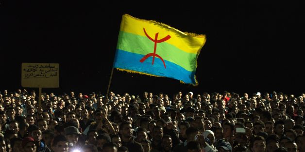 Protesters hold the Amazigh (Berber) flag as they shout slogans in the northern city of Al Hoceima on October 30, 2016, following the death of fishmonger Mouhcine Fikri, who was crushed to death on October 28 in a rubbish truck in Al Hoceima, as he reportedly tried to protest against a municipal worker seizing and destroying his wares.   Thousands of Moroccans on October 30 attended the funeral of the fishmonger whose gruesome death in a rubbish truck crusher has caused outrage across the North African country. An image of his inert body -- head and arm sticking out from under the lorry's crushing mechanism -- went viral on social media, sparking calls for protests nationwide including in the capital Rabat.  / AFP / FADEL SENNA        (Photo credit should read FADEL SENNA/AFP/Getty Images)