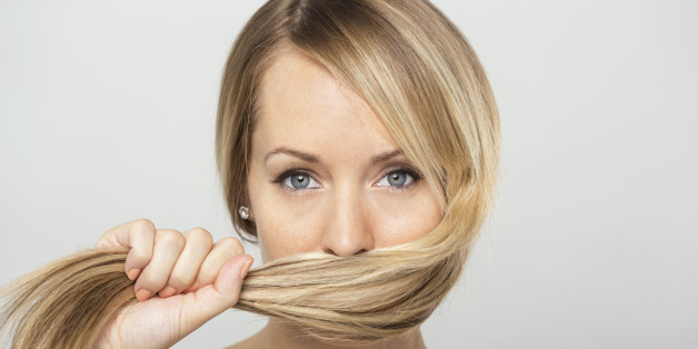 Portrait of blonde woman holding hair over face