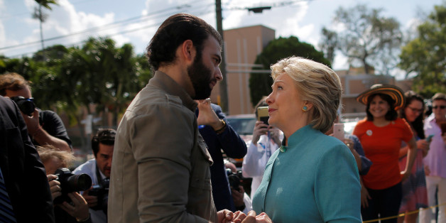 U.S. Democratic presidential nominee Hillary Clinton talks to actor and singer Jencarlos Canela while visitiing an early voting site in West Miami, Florida, U.S. November 5, 2016.  REUTERS/Brian Snyder