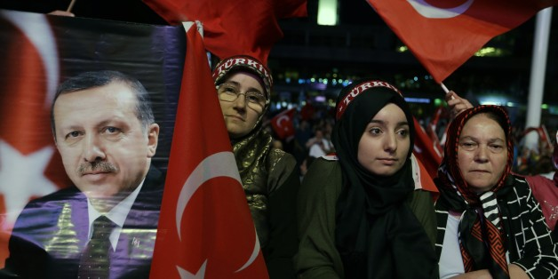 A woman holds a photograph of Turkish President Recep Tayyip Erdogan as others wave flags of their country during an anti coup rally at Taksim square in Istanbul, Wednesday, Aug. 10, 2016. The failed coup left more than 270 people dead and about 18,000 people have been detained or arrested. (AP Photo/Thanassis Stavrakis)