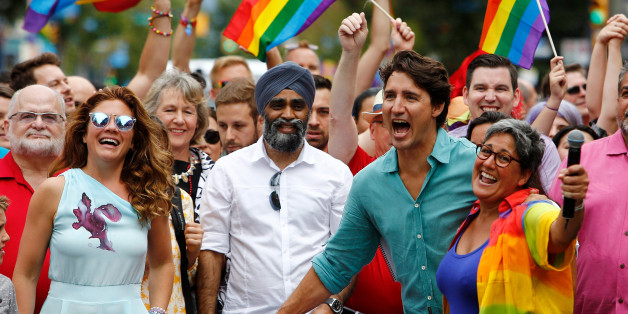 Canada's Prime Minister Justin Trudeau reacts as he and his wife Sophie Grégoire Trudeau (L) walk in the Vancouver Pride Parade in Vancouver, British Columbia, July 31, 2016. REUTERS/Ben Nelms