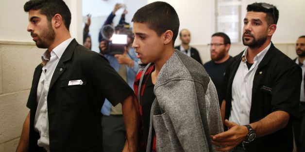 Ahmed Manasra (C), a 14-year old Palestinian boy, convicted of the attempted murder of two Israelis in a stabbing in October 2015, leaves the District Court in Jerusalem after his sentencing hearing on November 7, 2016.The court sentenced Manasra to 12 years in jail for the knife attack, his lawyer said. / AFP / AHMAD GHARABLI        (Photo credit should read AHMAD GHARABLI/AFP/Getty Images)