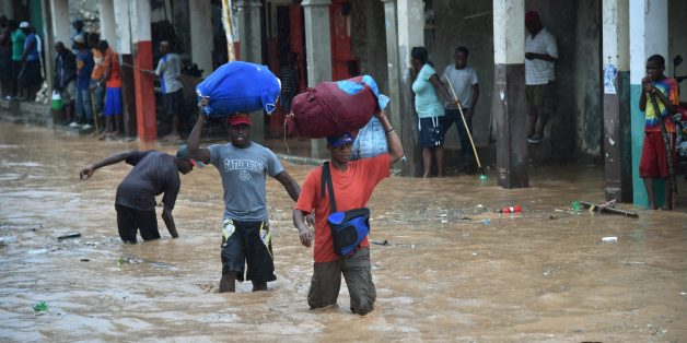 Haitian men navigate a partially flooded street during a seasonal storm on November 5, 2016 in the commune of Jeremie, southwestern Haiti, one of the cities hit hard by Hurricane Matthew.One month ago, on October 4, Haiti was hit by Hurricane Matthew where at least 546 people were killed, packing winds of 145 miles (230 kilometers) per hour. / AFP / HECTOR RETAMAL        (Photo credit should read HECTOR RETAMAL/AFP/Getty Images)