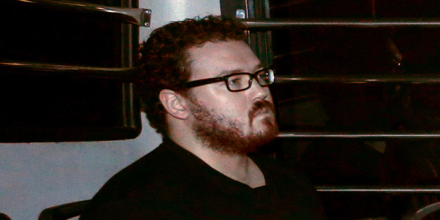 FILE PHOTO -  Rurik George Caton Jutting, a British banker charged with two counts of murder after police found the bodies of two women in his apartment, sitting in the back row of a prison bus as he arrives at the Eastern Law Courts in Hong Kong November 24, 2014. REUTERS/Bobby Yip/File Photo       TPX IMAGES OF THE DAY