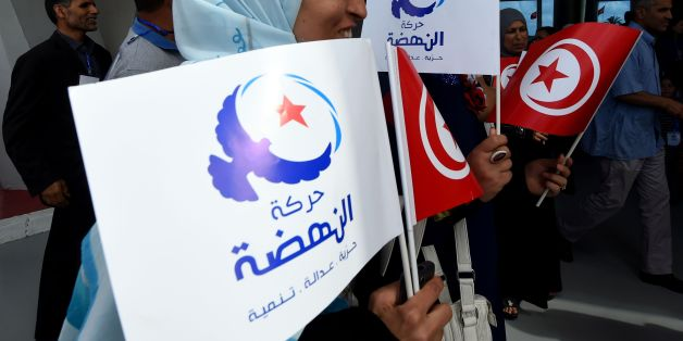 Supporters of Tunisia's Islamist Ennahdha Party wave the national and party flags on May 20, 2016 during the opening of Ennahdha's three-day congress in Tunis.Thousands of people attended the opening ceremony of the congress -- the first since 2012 -- held at a sports complex in Rades, south of the capital Tunis, amid heavy police security. / AFP / FETHI BELAID        (Photo credit should read FETHI BELAID/AFP/Getty Images)