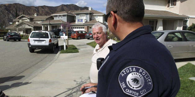 Resident Lorenzo Tatone (L) speaks to an Azusa police gang detective giving evacuation orders to residents in preparation against possible flash floods and mud slides in the second, and larger, of two storms to hit drought-plagued California this week in Azusa, California, February 27, 2014. The arrival of rain brings both minor relief from the third year of the worsening California drought and the threat of disastrous debris flows below mountainsides charred and hardened by an unseasonal wildfire, deemed the Colby Fire, that destroyed or damaged about two dozen homes, injured six people and sent thousands fleeing last month. Though welcomed, the rain is not expected to be enough to end the record historic conditions. REUTERS/David McNew      (UNITED STATES - Tags: ENVIRONMENT)