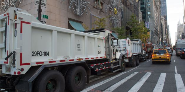 New York City Department of Sanitation trucks form a protective barrier around the Trump Tower on Fifth Avenue, November 8, 2016 in New York.  / AFP / US-VOTE / Bryan R. Smith        (Photo credit should read BRYAN R. SMITH/AFP/Getty Images)