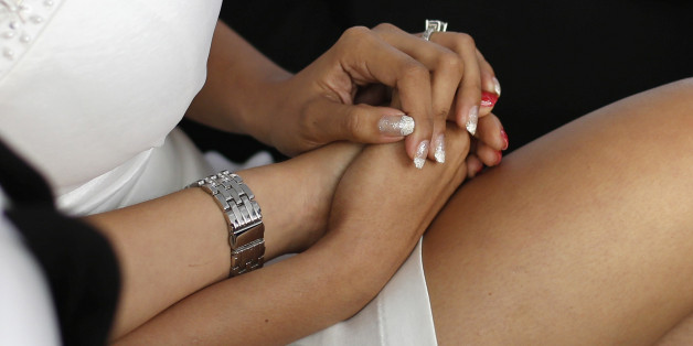A lesbian couple hold hands during a mass wedding ceremony in Mexico City June 28, 2014. About 119 couples tied the knot in the event organized by the Miguel Hidalgo borough, local media reported. REUTERS/Bernardo Montoya (MEXICO - Tags: SOCIETY)
