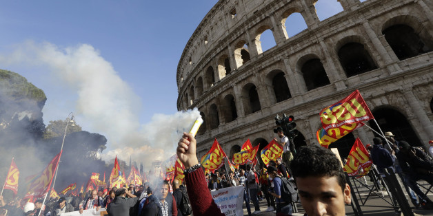 People march through downtown Rome to protest Matteo Renzi's government politics, Saturday, Oct. 22, 2016. In background is the Colosseum. ( AP Photo/Andrew Medichini)