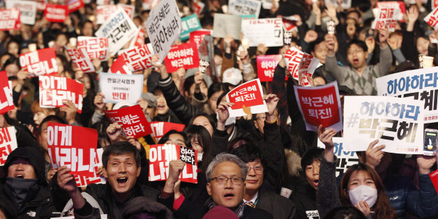 """South Korean protesters shout slogans during a rally calling for South Korean President Park Geun-hye to step down in downtown Seoul, South Korea, Saturday, Nov. 5, 2016. Tens of thousands of South Koreans poured into the streets of downtown Seoul on Saturday, using words including """"treason"""" and """"criminal"""" to demand that Park step down amid an explosive political scandal. The signs read """"Park Geun-hye should step down."""" (AP Photo/Ahn Young-joon)"""
