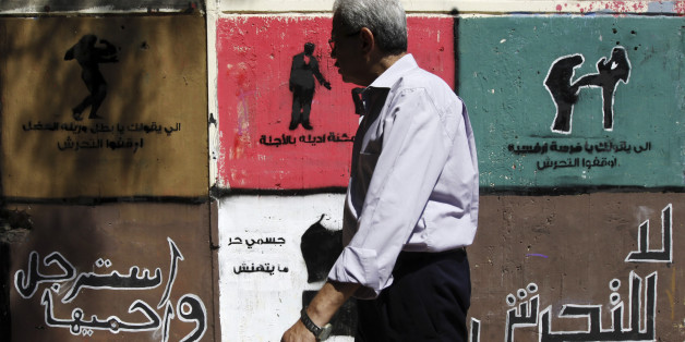 "A man walks past anti-sexual harassment graffiti along Mohamed Mahmoud street near Tahrir Square in Cairo, September 26, 2012. The graffiti on the walls of Mohamed Mahmoud Street had existed since November 2011, where some of the fiercest fighting between protesters and security forces took place. The Arabic words read, ""No harassment - Be man and Protect her"". REUTERS/Amr Abdallah Dalsh  (EGYPT - Tags: POLITICS CIVIL UNREST)"