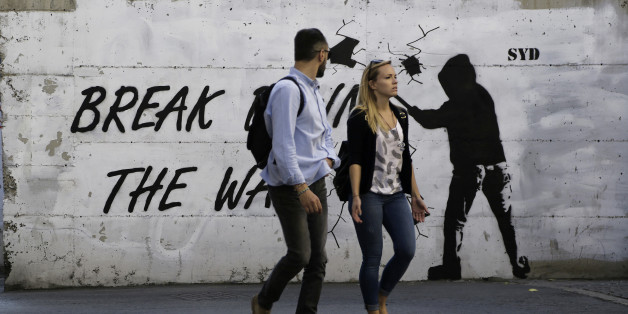 """A couple walk in front of a wall with graffiti, near the UN buffer zone, """"Green Line"""" that divide the Greek and Turkish Cypriot controlled areas in divided capital Nicosia in this eastern Mediterranean island of Cyprus, Friday, Nov. 11, 2016. The rival leaders of ethnically divided Cyprus are locked in crucial talks in Mont Pelerin, Switzerland that will determine whether a peace deal is within reach. (AP Photo/Petros Karadjias)"""
