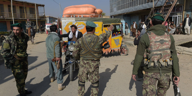 Afghan security personnel stop people as they block the road near the largest US military base in Bagram, 50 km north of Kabul, after an explosion on November 12, 2016. Four people were killed November 12 in an explosion inside the largest US military base in Afghanistan, NATO said, with local officials blaming a suicide attacker posing as a labourer for the major security breach. / AFP / SHAH MARAI        (Photo credit should read SHAH MARAI/AFP/Getty Images)